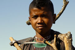 Hard working poor boy carrying a tree trunk - MADAGASCAR Stock Photography