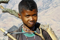 Hard working poor boy carrying a tree trunk - MADAGASCAR Royalty Free Stock Photo