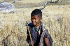 Hard working poor boy carrying a tree trunk - MADAGASCAR Royalty Free Stock Image
