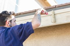 Meticulous Professional Painter Using Small Roller to Paint House Fascia Stock Image