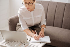 Hard working serious woman making notes. Plan for the day. Hard working serious confident businesswoman sitting in front of her laptop and making notes while Royalty Free Stock Photos