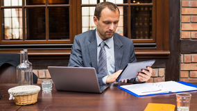 Hard working smiling businessman in restaurant with laptop and pad. Stock Photography