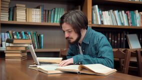 Hard-working Student in Library. Hard-working caucasian student studying in library, young man with beard and straight fair hair using laptop while reading book stock video