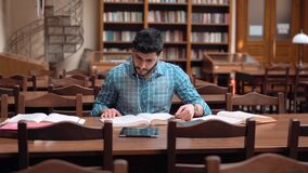 Man in the Library. Hard-working student studying at brown desk in the library, good-looking asian man searching for information in books, doing home assignment stock video