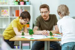Smart bearded teacher pointing on pictures and explaining meaning. Hard-working students. Smart bearded teacher pointing on pictures and explaining meaning to royalty free stock photo