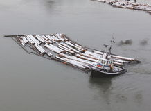 Hard Working Tugboat. A tug boat covered in a dusting of snow on a river hauls a boom Royalty Free Stock Photo