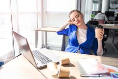 Hard-working woman is sitting at the table and has some rest. She is bored and tired. Woman has a cup of coffee in her. Hands. Also she is stretching with her Royalty Free Stock Image