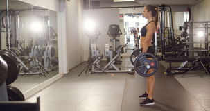 Hard working woman training deadlifts with heavy weights in fitness gym