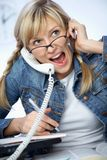Hard-working young blonde. Crying to phone Stock Image