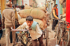 Hard working young man carries heavy bags of cargo on vintage bicycle Royalty Free Stock Images