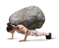 Hard workout. Muscular woman lifts a boulder with back Royalty Free Stock Image