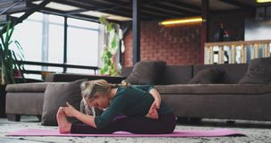 Hard yoga exercises in the morning attractive young lady practicing to stretching the body , for energy and for a health stock footage