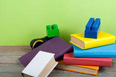 Hardback colorful books, toy, shoes on wooden table. Back to school. Copy space for text. Education business concept. Royalty Free Stock Photo