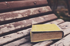 Hardback old book on wooden bench in autumn park Royalty Free Stock Photography