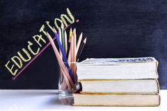 Hardback and textbook stacked with pencils on the table on the b. Lackboard background. The concept of intelligence comes from education. focused on the textbook Stock Images