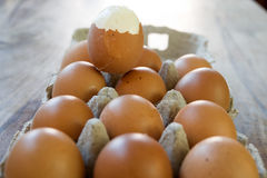 Hardboiled egg partly shelled. On a series of raw eggs Royalty Free Stock Photography