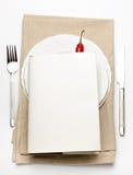 Hardbook encima de una placa con el cuchillo y la fork Foto de archivo libre de regalías