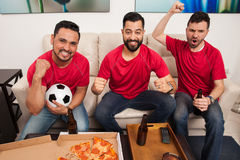 Hardcore soccer fans celebrating. Wide angle portrait of three male friends and soccer fans celebrating a goal and a victory while watching the game on TV Stock Image