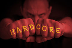 HARDCORE written on an angry man's fists. HARDCORE written on the fingers of an angry man's fists. Red colored. Message concept image Royalty Free Stock Images
