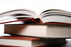 Hardcover books. Three hardcover books with one open towards the middle of the book, focus on binding Stock Photos
