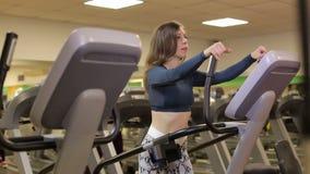 Harde cardiotraining Het jonge sportieve meisje doet op orbitrek bij de gymnastiek stock videobeelden