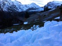 Harde lichtblauwe sneeuw dichte omhooggaand op de heuvel met de achtergrond van de bergmening in wintertijd stock afbeelding