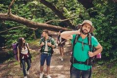 Harde, moeilijke, vermoeiende en uitputtende expeditie van vier vrienden in wild bos in sleep De kerel worstelt van een halspijn, stock afbeeldingen