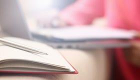 Harde vrouwen de studie schrijft informatie aan notitieboekje neer stock fotografie
