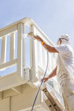 Harde Werkende Schilder Spray Painting een Dek van een Huis Stock Fotografie