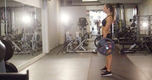 Harde werkende vrouw die deadlifts met zware gewichten in geschiktheidsgymnastiek opleiden stock footage