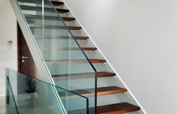 Hardened glass balustrade in house. Detail of hardened glass balustrade in house with wooden stairs Stock Images