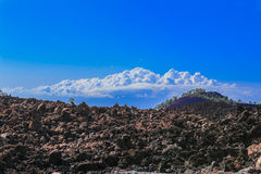 Hardened lava of the volcano on the background of blue sky. Royalty Free Stock Images