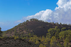 Hardened lava of the volcano on the background of blue sky. Stock Photo