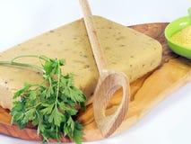 Hardened polenta on wooden olive chopping board. Hardened polenta on a wooden olive chopping board Royalty Free Stock Photo