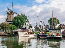 Harderwijk harbor and windmill, Holland. Windmill, bridge and boats in the harbour of Harderwijk, Netherlands Stock Photos