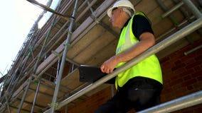 Αρσενικός εργάτης οικοδομών επιστατών οικοδόμων για το εργοτάξιο που φορά hardhat που γράφει στην περιοχή αποκομμάτων απόθεμα βίντεο