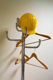 Hardhat. Yellow hardhat is hanging on a coat rack with hangers Stock Image
