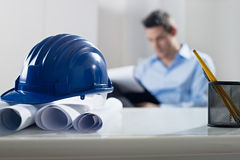 Hardhat and blueprint on desk Royalty Free Stock Image