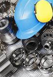Hardhat and engineering parts. Hardhat, helmet, surrounded by gears, pinions and cogs, engineering parts Royalty Free Stock Photos