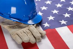 Hardhat And Gloves On American Flag. Close-up Of Blue Hardhat And Gloves On American Flag Stock Photos