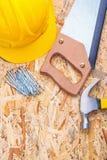 Hardhat nagelt Handsawtischlerhammer auf plyboard Lizenzfreie Stockfotografie