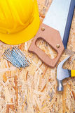 Hardhat nails handsaw claw hammer on plyboard Royalty Free Stock Photography