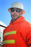 Hardhat Supervisor. An older unshaven labor supervisor wearing a white hardhat, sunglasses and an orange construction caution hooded sweat shirt Stock Images