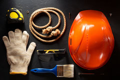 Hardhat und Werkzeuge auf Schwarzem lizenzfreie stockbilder