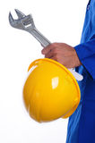 Hardhat and Wrench In Hand. A close up of a man's left hand holding a yellow hardhat and wrench. The man is wearing a royal blue jumpsuit Stock Photo