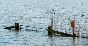 Hardinxveld,荷兰- 2018-01-14:有芦苇的门和签署涌来的河前陆 免版税库存照片