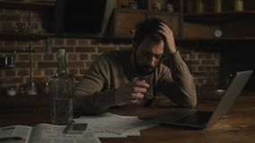 Upset man with laptop and alcohol. Hardships. Distressed young man sitting at the table and drinking alcohol while looking at payment bills and using a laptop stock footage