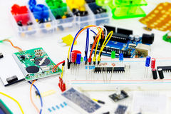 Hardware engineer`s workplace. Prototype board with microcontrollers, chips, resistors and light-emitting diodes on white desktop of hardware engineer Royalty Free Stock Images