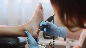 Pedicurist master removes old skin on client`s heel making hardware pedicure. Hardware pedicure in beauty salon. Professiomanl pedicurist master in blue gloves stock video