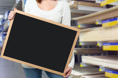 Hardware Store. Young woman holding blank blackboard at a hardware store Royalty Free Stock Photos